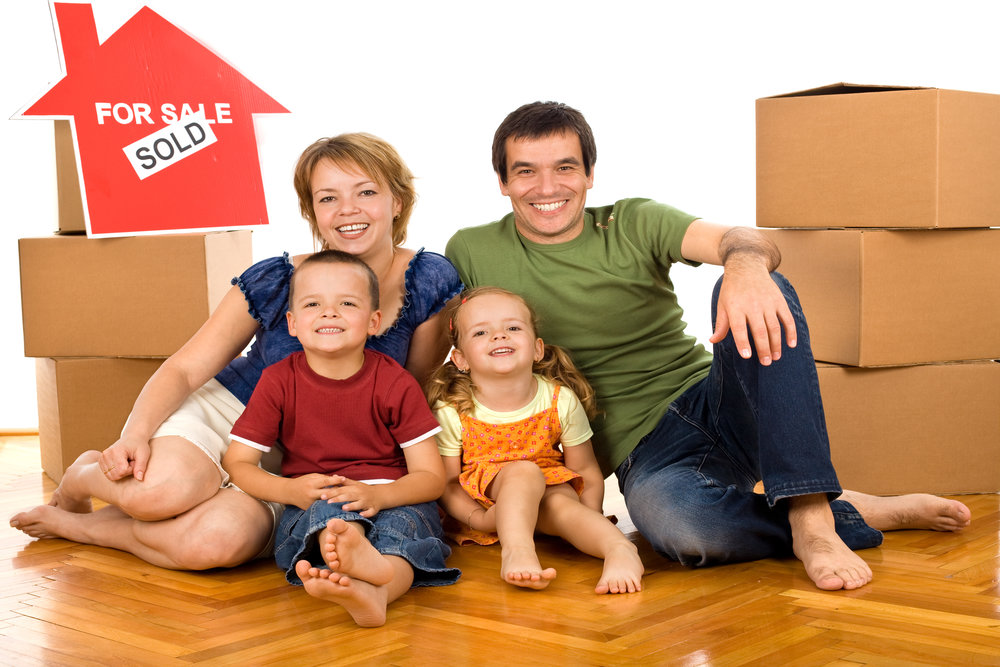 Happy Family With Cardboard Boxes Moving In A New Home